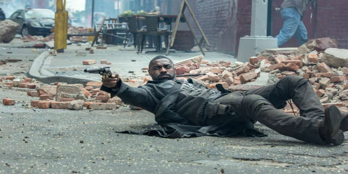 Idris Elba laying on the ground and firing his pistol from The Dark Tower