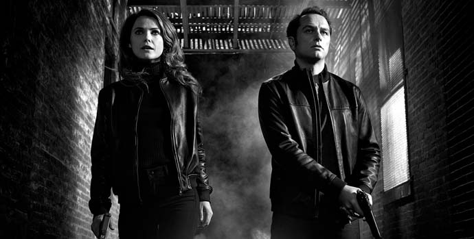 Phillip and Elizabeth Jennings holding guns and looking like secret agents