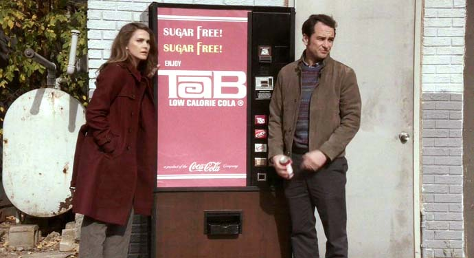 Elizabeth and Phillip Jennings in front of a Tab Cola Machine circa 1981